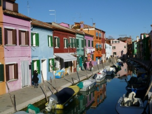 The colorful houses of Burano, relfected in a canal.  Everyone has a boat.