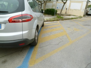 Here we see a car parked in blue stripes (pay) but overlapping onto yellow (reserved in this case for handicapped).