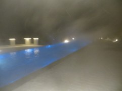 Steam rises from the infinity pool while snow falls.