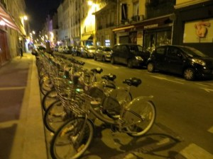 Velib bikes all tucked away at night. During the day the racks were empty, all bikes in use.