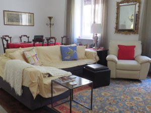 "We have a large ""sala,"" a combined living room and dining room. Some of our landlady's antiques combined with our comfy recliner, our rugs, and a modern sofa."