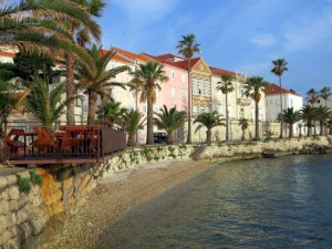 Along the Korčula waterfront in the morning, soft light, pastel colors.