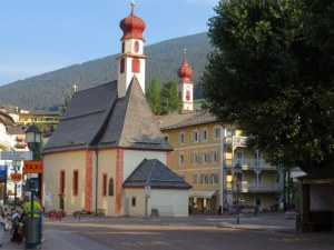 Ortisei in the morning. The two steeples look the same size from this perspective, but the closer one is a fraction of the size of the big church on the hill.