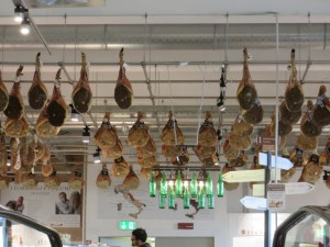 Prosciutti hang from the ceiling at the top of a moving ramp leading to the salumi department.
