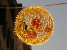 Sparkling ball, one of a series hung above one small street.
