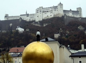 Golden Orb Guy statue in Salzburg, gazing up at the fortress.