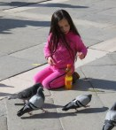 The pigeons were keeping this little girl occupied.