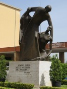 "Statue at the Don Orione complex. The base says ""I always bend to the needs of my neighbor."""