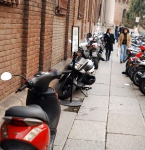 Not unusual to see the sidewalk as a parking lot for motorini, and frequently one or more are in motion.