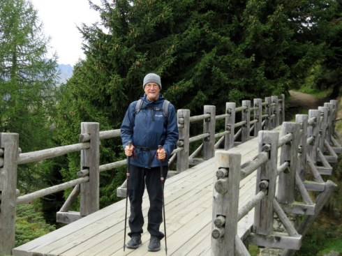 Man on bridge with hiking sticks